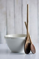 Old wooden spoons beside ceramic basin