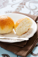 Whole and halved bread roll on plate 22199063356| 写真素材・ストックフォト・画像・イラスト素材|アマナイメージズ