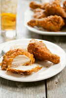 Two Pieces of Battered Fried Chicken on a Plate; One Piece C