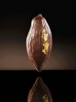 A cocoa bean-shaped chocolate praline with leaf gold