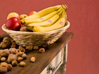 Organic bananas and apples in a basket in a wooden table wit