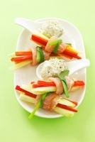Cucumber and pepper sticks with raw ham and a cheesey dip