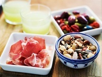 Glasses of absinth with ham, olives and nuts