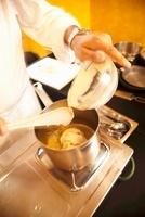 A cook preparing white bean soup
