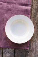 An empty plate on a purple cloth