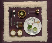 A festive place setting with pea soup and rice pudding frame