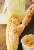 Corn cobs being spread with chilli and lemon butter
