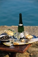 Champagne, olives and bread with fresh cream on a table by t