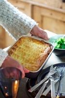 A woman serving shepherds pie