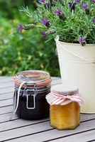 Blackberry jam and a jar of honey on a garden table