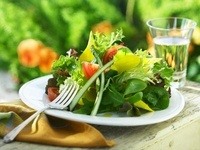 Fresh Spring Salad on Outdoor Table; Glass of Water