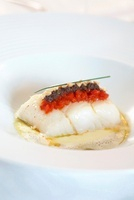 Cod on a bed of potato and olive cream with peppers and pean