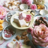Different sorts desserts and candies decorated with rose pet