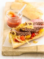A steak sandwich with onions and peppers