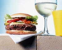 A hamburger, a glass of water and a plastic cup with a straw