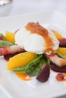 Poached egg on a herb salad with bacon and oranges