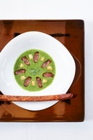 Creamy soup with lamb's lettuce and peppered sausage