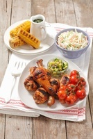 Grilled chicken legs with cherry tomatoes, coleslaw and corn