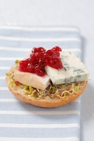 Half a bread roll topped with bean sprouts, blue cheese and