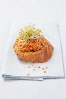 A crostino topped with tomato tapenade and bean sprouts