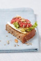 Wholemeal bread topped with chicory, beetroot paste, sunflow