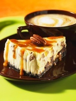 A slice of caramel cheesecake with pecan nuts and a cafe lat