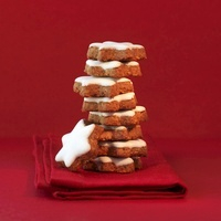 A stack of star shaped cinnamon cookies with red ambiance