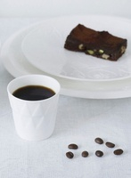 Coffee, coffee beans and a pistachio brownie