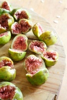 Fresh figs, halved, on a wooden board