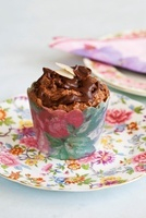 A chocolate cupcake in a paper case printed with flowers