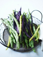 Green, yellow and purple beans in a wire basket