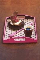 A stuffed chocolate rabbit and coffee on a tray