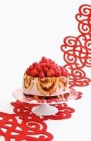 An ice cream cake with sponge rolls and fresh berries