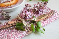 A napkin, cutlery and lilac tied together