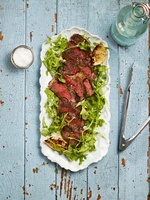 Sliced rib-eye steak with rocket on a serving dish