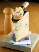 A slice of Stilton with a knife and cheese bread