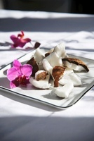 Coconut pieces and an orchid on a plate
