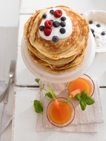 Carrot drinks and pancakes with yoghurt and berries