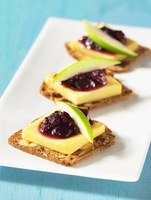 Crackers topped with cheese, blueberry chutney and apple wed
