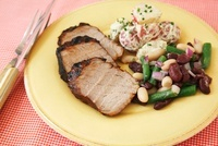 Roast Pork Slices with Bean Salad and Potato Salad on a Plat