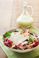 Bowl of Pear Salad with a Small Pitcher of Dressing