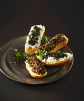 Bread rolls topped with olives, cream cheese and herbs