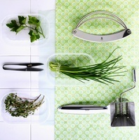Fresh herbs, a chopping knife, herb scissors and a herb mill