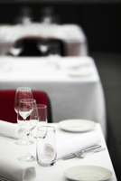 Three tables in a restaurant laid with white cloths