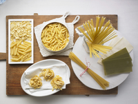 Various types of pasta on a chopping board