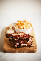Barbecue Pork Ribs on a Cutting Board with a Bowl of Macaron
