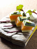 Salmon cubes with cucumber and beetroot leaves