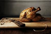 A Whole Roasted Chicken on Cutting Board 22199074406| 写真素材・ストックフォト・画像・イラスト素材|アマナイメージズ