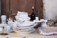 Plates, cups, glasses, tea towels and wine bottles on a rust