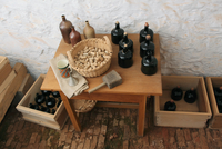 Various bottles made of clay and black ceramic next to a bas